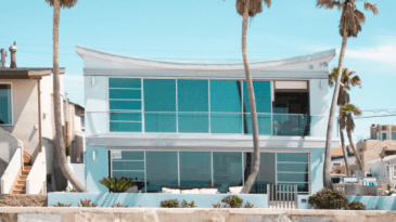 Two Floor Beautiful Beach House With Big Windows During Sunny Day