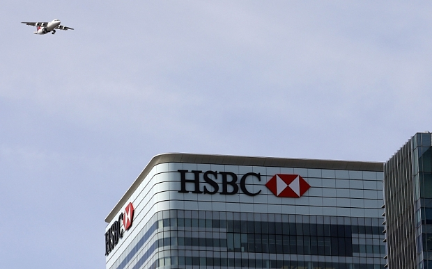 A plane flies past the HSBC building in Canary Wharf, London April 17, 2015.  HSBC and Standard Chartered are looking at the viability of quitting London for a new home in Asia because a big jump in a tax on UK banks makes staying in Britain increasingly painful. Several investors told Reuters they want the two banks to do a thorough analysis on whether it makes sense to move after Britain raised the bank tax by a third last month. REUTERS/Cathal McNaughton