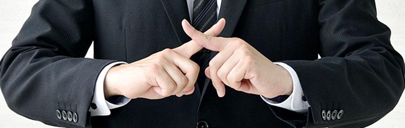 指でバツを出す男性