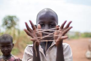 Child making a cats cradle - Alex Radelich - Unsplash