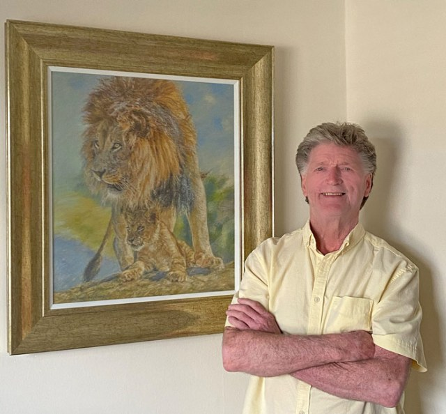 Michael Hepburn standing in front of one of his framed paintings of lions.
