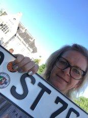 Sylvia hält Kennzeichen mit Plakette
