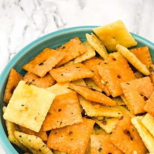 yellow and white cheese crackers with ranch and pepper coating in blue bowl