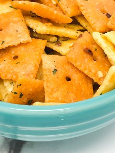 White and yellow crackers coated in a spicy mix in a blue bowl.