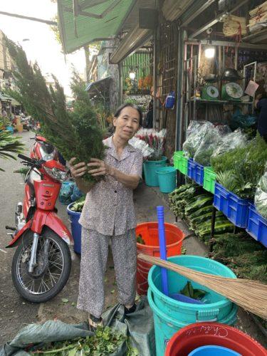 Vendor displays cypress sprigs at Ho Thi Ky flower market