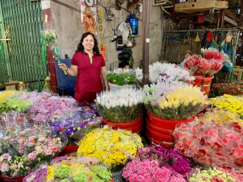 Vendor displaying flowers at Ho Chi Minh City's Ho Thi Ky market