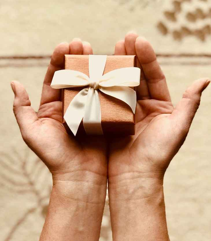 two hands presenting tiny gift