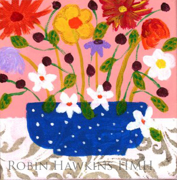 a little blue vase with flowers and a stenciled white tablecloth. White, purple, red, yellow and orange flowers.