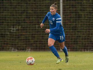 Finland's Natalia Kuikka dribbles the ball on a rainy pitch.