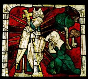 Detail of a medieval glass-stained window of a clergyman healing a blind woman by putting his hand over her eyes. Photo copyright: Historic England