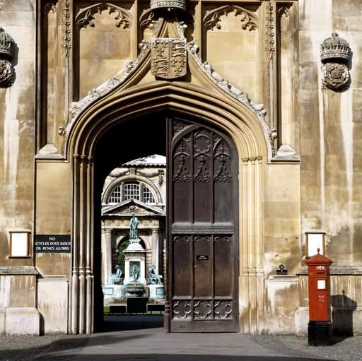 An example of a JW Penfold post box design standing at the entrance of King's College, Cambridge. It is a mid-19th century cast-iron hexagonal box with decorated cap and 'VR' insignia. It is listed at Grade II.