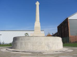 The British Thomson Houston Company commissioned a War Cross - one of 15 broadly similar Lutyens' designs characterised by a tall minimalist shaft and a very short cross arm - standing on a circular plinth carved with the 243 names of employees who died in the war. It was positioned immediately outside their factory in Mill Road, Rugby. (The location where Frank Whittle's ground-breaking prototype jet engine was manufactured in the 1930s). During construction, a time-capsule box containing company artefacts and war records was buried underneath the memorial. It was unveiled on 28 October 1928. The British engineering firm made electric motors, generators, steam turbines and light bulbs. It expanded production during the First World War to provide the Royal Navy with lighting, signalling and radio gear. In 2010, the memorial, plus time-capsule, was relocated 400 metres away due to impending redevelopment, but it is still within the engineering works site. It was re-dedicated 22 July 2010. Photo courtesy of Tim Skelton