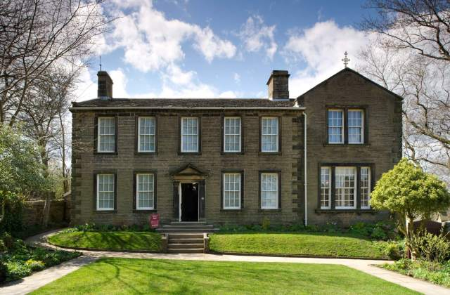 Haworth Parsonage, Haworth, West Yorkshire, listed Grade I. Home to Patrick Brontë and his three literary daughters Charlotte, Emily and Anne from 1820 onwards. The sisters' most famous novels were written here, including Charlotte's Jane Eyre, Emily's Wuthering Heights and Anne's Agnes Grey, all in 1847. Charlotte died in the Parsonage on 31 March 1855. (c) Historic England
