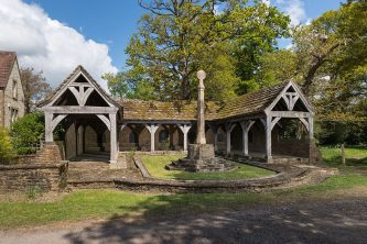 Blackmoor War Memorial Cloister, Hampshire. Unveiled in 1920. Upgraded to Grade II*. This memorial was commissioned by Lord and Lady Selborne in memory of their second son, Captain Robert Palmer, killed in Mesopotamia, January 1916. The vernacular design draws on the Arts & Crafts tradition; its simple timber framing reminiscent of an ancient agricultural building. It takes the form of a three-sided cloister, enclosing a garden with a memorial stone cross as a focus. Commemorative bronze plaques are fixed to the Cloister's interior wall, remembering both Captain Palmer and the dead of the village in both world wars. A memorial fountain sits in a niche, flanked on one side by a War plaque, showing a leafless tree above, and on the other a Peace plaque with a tree in full leaf with blossoms. The fountain was intended to be a water supply for the next door school's children who would: '…provide animation and lively activity, uniting the dead and the living future of the village.'