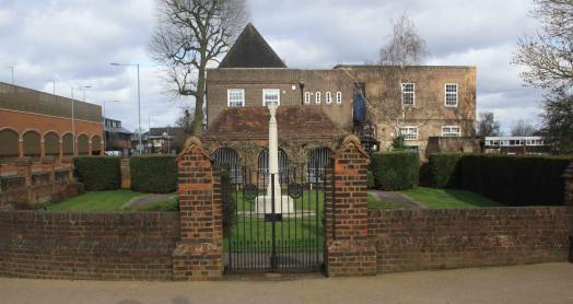 Hatfield War Memorial, Hertfordshire. Unveiled 12 June 1921. Newly graded at Grade II*. Herbert Baker designed this brick-walled memorial garden, with its Portland stone cross, gates and pavilion, as a permanent testament to the sacrifice of local people who lost their lives in the First World War. The cross, like others designed by Baker, is encircled with carved stone roses and lilies, representing England and France, that trail down the top of the shaft. The garden pavilion, which is reminiscent of the shelter buildings that Baker designed for the cemeteries of the Western Front, was intended as a place to give protection to visitors from the weather. Stone tablets within are inscribed with names of the dead of both world wars. A beautifully carved band above carries a biblical quote from 1 Corinthians 15: ' THANKS BE TO GOD WHICH GIVETH US THE VICTORY…'