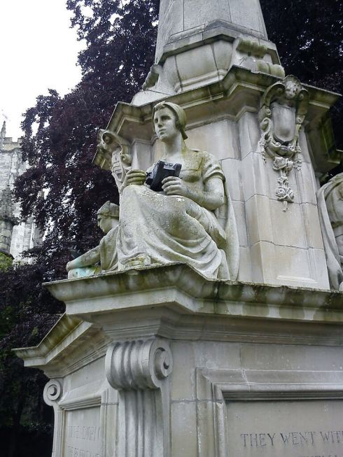 Four seated stone figures represent the Army, Navy, Air Force and medical services. Each holds a symbol, respectively a tank, ship, airplane and the staff of Esculapius - a Greek deity associated with healing © War Memorials Trust