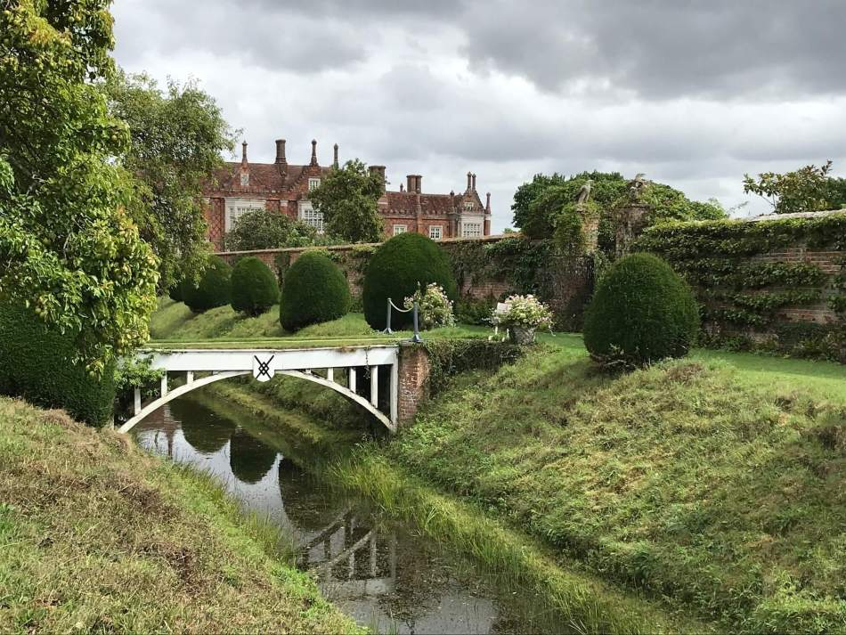 A small white bridge over a river with Helmingham Hall in the background