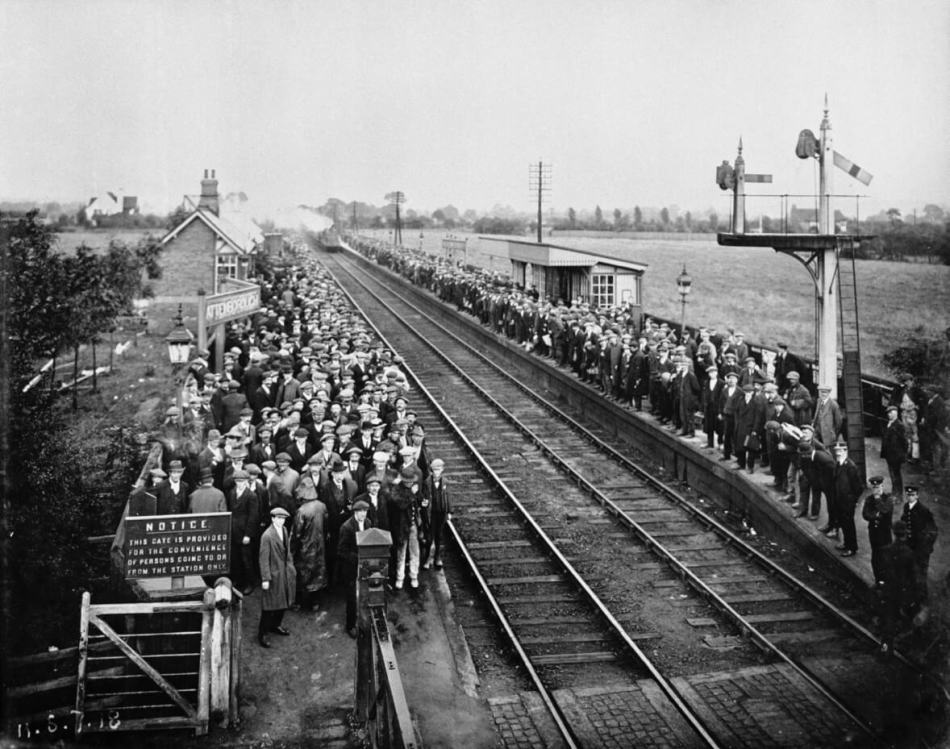 Crowds of workers stand precariously beside a train track, waiting for their train to the factory