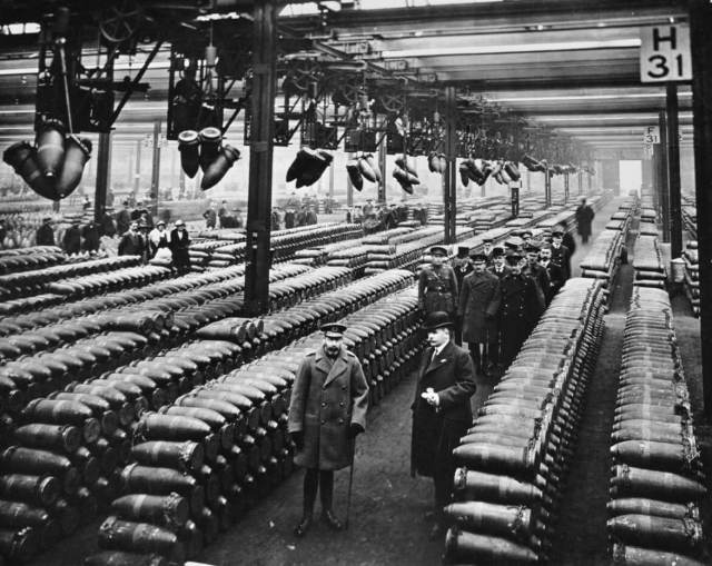 King George visiting Chilwell Factory, surrounded by stacked munition shells