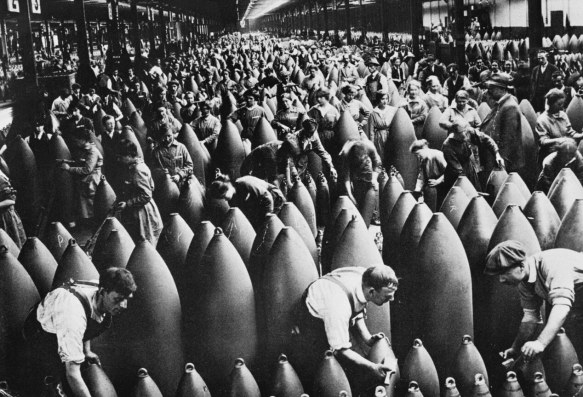 Factory workers finishing large shell munitions with paint or varnish