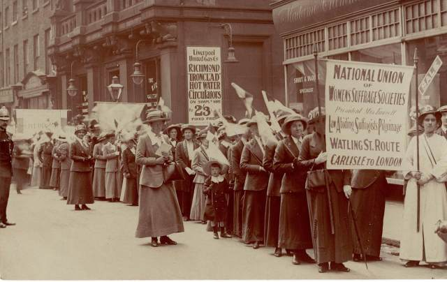 Suffragettes march through the streets of Liverpool with banners and flags aloft