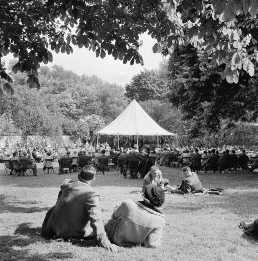 A young couple relax on the grass near to a canvas bandstand