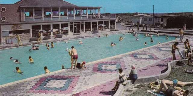 An old postcard image of the lido at Caister Holiday camp with children and parents sunbathing and swimming