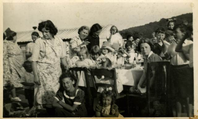 Women and children gather around a table with food