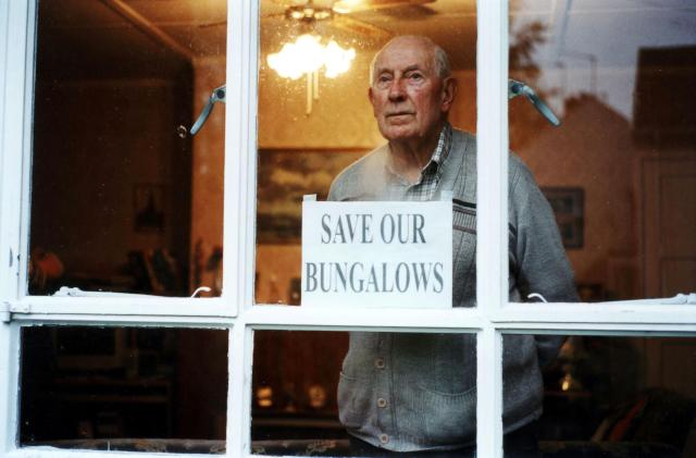 A man stands in a window with a sign on it that says 'save our bungalows'