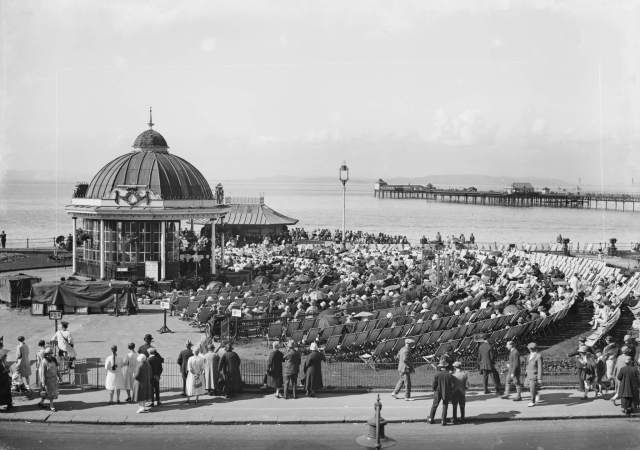 People on deck chairs look on at a bandstand on the coast