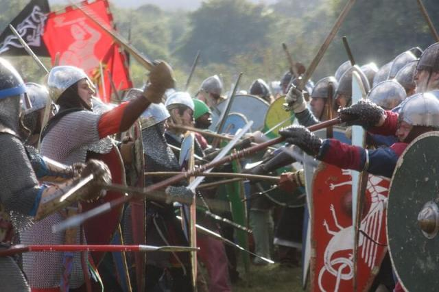 Reenacters in elaborate medieval costume imitate fighting with wooden swords