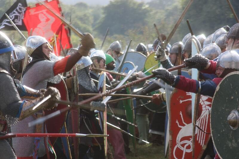 Reenacters in elaborate medieval costume imitate fighting with wooden swords