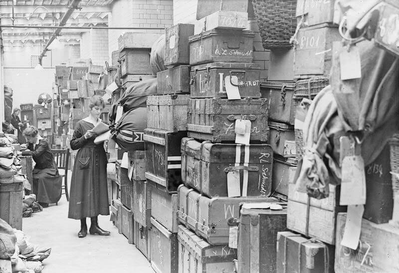 A woman looks at paperwork next to a huge stack of suitcases and bags