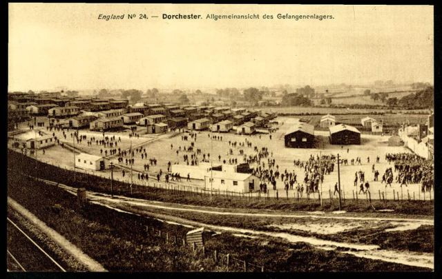 Aerial view of POW camp with temporary housing seen and a large open area with lots of people in situ