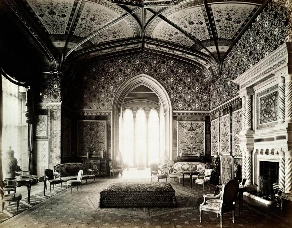 Black and white image of the opulantly decorated drawing room at Eaton Hall, with various lounge chairs and writing desks