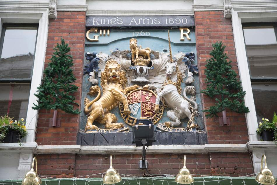Crest featuring a lion and a unicorn, script above reads Kind's Arms 1890