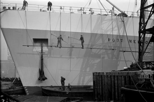Men paint a ship's hull at Tilbury Docks