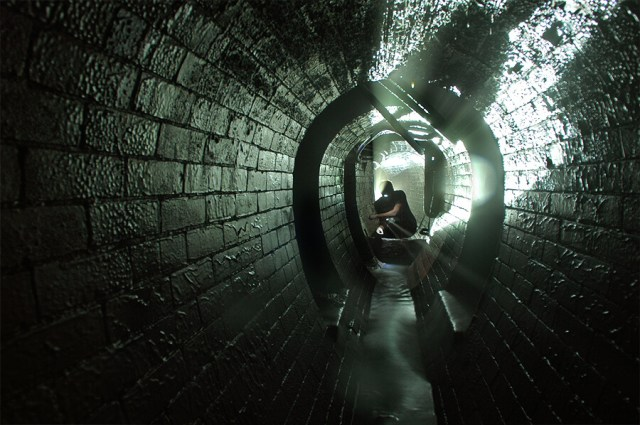 Contemporary image of a street sewer - egg shapes with a narrow walkway ath the bottom. A person can be seen wearing a head torch