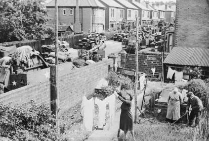 Local people in their garden at Southampton while military equipment passes by en route for embarkation to Normandy © IWM NYT27247