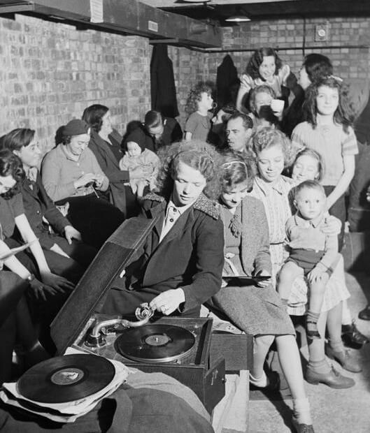 A woman plays a gramophone, and others can be seen knitting and reading in an air raid shelter