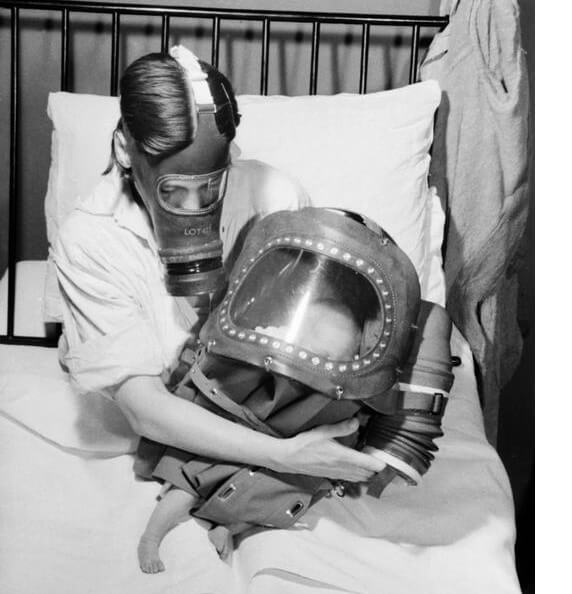 A mother in a gas mask holds her new born child whose feet are poking out of a baby gas helmet.