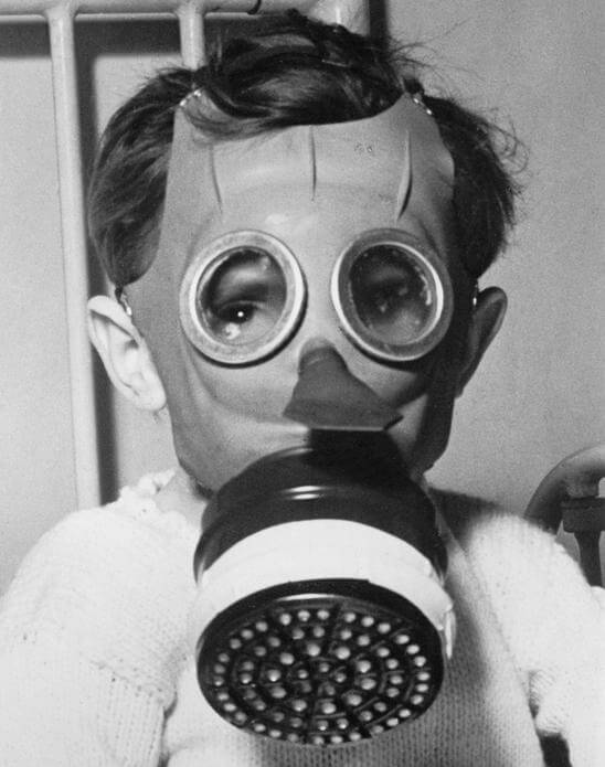 A young boy wears a 'Mickey Mouse' gas mask