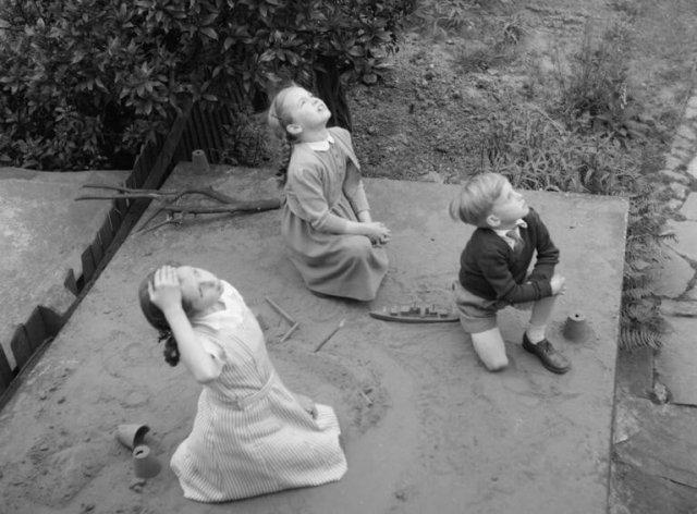 Children sitting on an air raid shelter watch aircraft pass over their garden