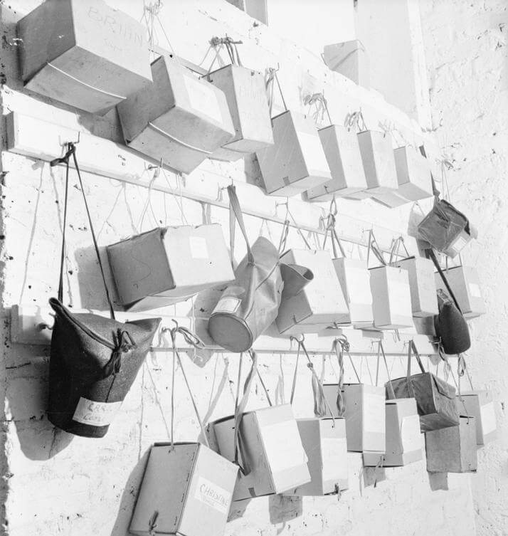 Gas mask boxes and cases hanging in a nursery