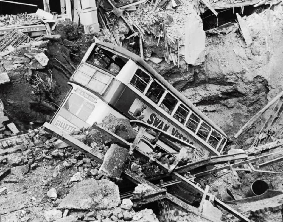 A bus lies in a bomb crater following an air raid, Balham