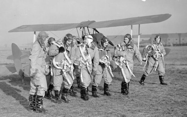 The first pilots of the ATA walking past newly completed Tiger Moths awaiting delivery © IWM C382