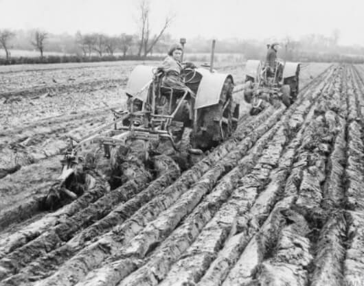 Land Girls ploughing a field with tractors on a farm in Hertfordshire. Machinery was often in short supply and ploughing was also done the traditional way using horse-drawn hand ploughs.