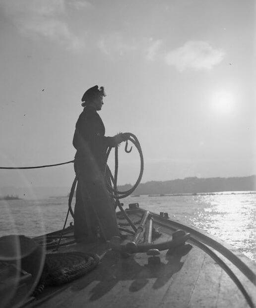 Wren coxswain, June Saunders, stands ready to moor her launch, Plymouth, Devon, November 1944