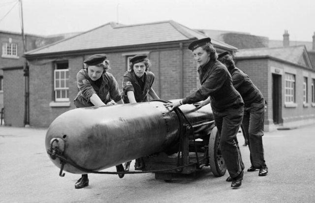 Four Wrens move a torpedo for loading onto a submarine at Portsmouth, Hampshire, 29 September 1943