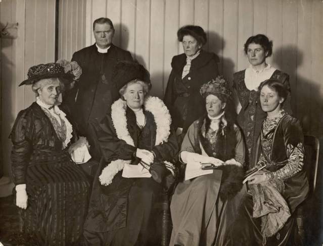Debate between Suffrage & Anti-Suffrage Societies held at Free Trade Hall, Manchester 1909. Sitting: Mrs Arthur Somerwell, Mrs Humphrey Ward, Miss Margaret Ashton, Mrs Helena Swanwick. Standing: Dean of Manchester. Miss - Gladstone, Mrs Margaret Hills (née Robertson). Image via LSE Library